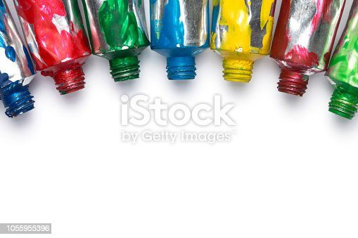 istock Artistic background. Acrylic colourful paint tubes isolated on white background with copy space. Cut out. 1055955396