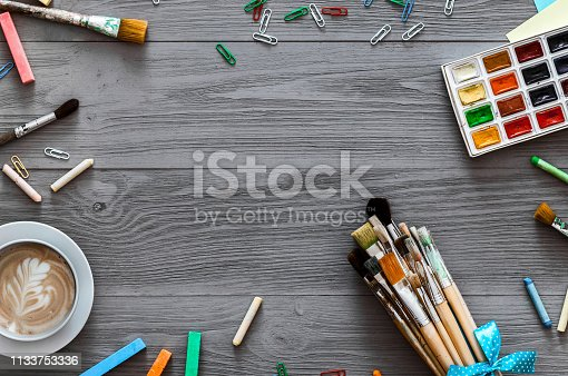 1134879628 istock photo Artistic background concept, creative art work accessory colorful supplies set, paint brushes, paints with coffee on grey gray wooden table, drawing lesson education, top view, flat lay, copy space 1133753336