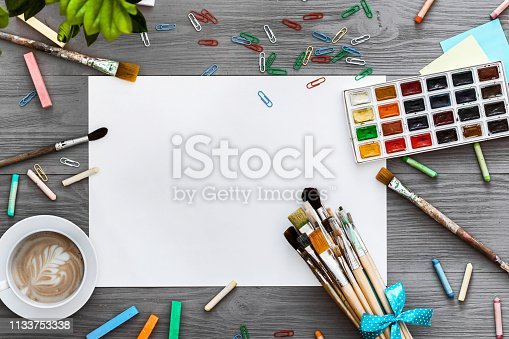1134879628 istock photo Artistic background concept, creative art work accessory colorful supplies set, paper, paint brushes, paintbox with watercolors on grey wooden table, drawing education, top view, flat lay, copy space 1133753338