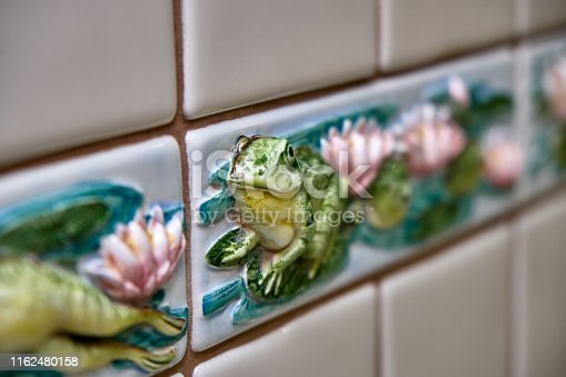 Artistic ceramic tiles with frogs and lotus in luxury bathroom. Close-up in soft focus