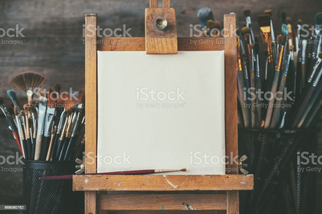 Artistic equipment in a artist studio: empty artist canvas on wooden easel and paint brushes Retro toned photo. stock photo