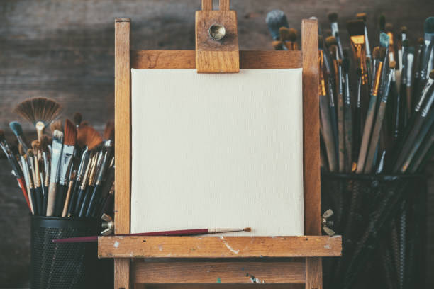 Artistic equipment in a artist studio: empty artist canvas on wooden easel and paint brushes Retro toned photo. - foto de acervo