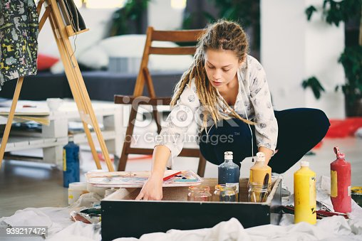 937313030 istock photo Artistic girl choosing colors for painting. 939217472