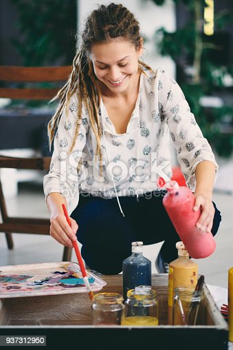 937313030 istock photo Artistic girl mixing colors for painting. 937312950