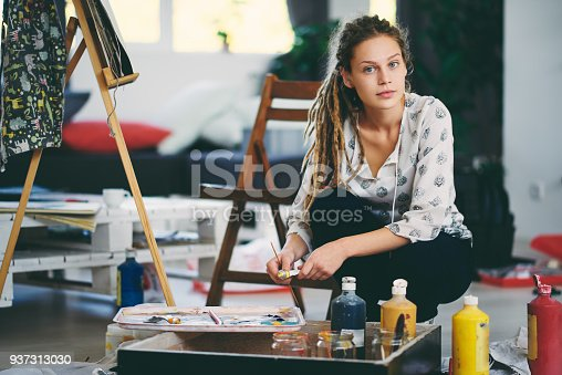 937313030 istock photo Artistic girl mixing colors for painting. 937313030