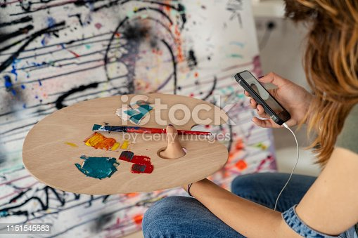 937313030 istock photo Artistic girl reading message 1151545583