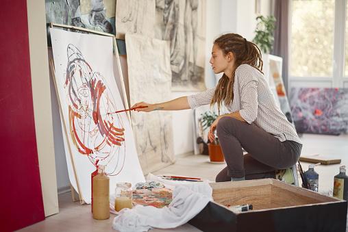 Künstlerische Mädchen Sitzt Im Studio Und Malen An Der Staffelei Stockfoto und mehr Bilder von Atelier