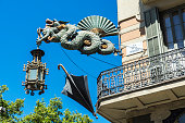 Lamppost decorated with a dragon, a fan and an umbrella in Les Rambles of Barcelona, Catalonia, Spain