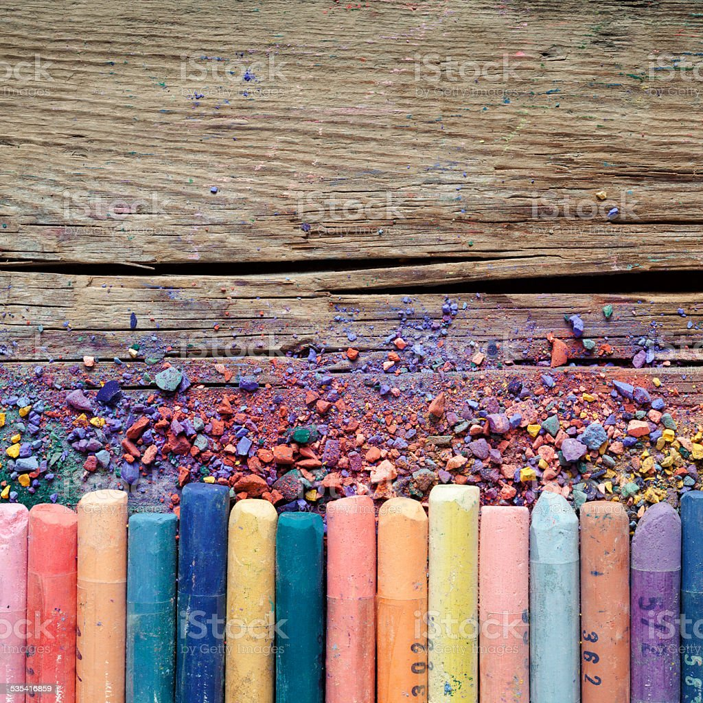 Artistic pastel crayons and pigment dust on wooden background stock photo