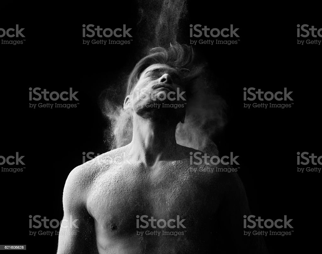 Artistic portrait of man in motion with powder splash stock image