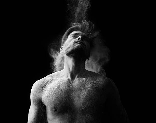 Artistic portrait of man in motion with powder splash Artistic portrait of man in motion with powder splash black and white photo irradiation stock pictures, royalty-free photos & images