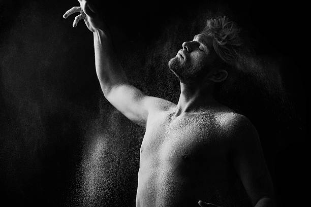 Artistic portrait of man in motion with powder splash Artistic portrait of man in motion with powder splash black and white photoArtistic portrait of man in motion with powder splash black and white photo irradiation stock pictures, royalty-free photos & images