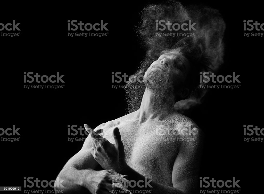 Artistic portrait of man in motion with powder splash stock photo