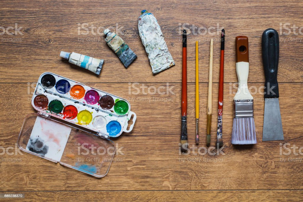 Artistic squirrel brushes, tubes of oil paints and watercolors on a wooden background.The palette of twenty-four colors .Used tools for artists and schoolchildren. Tools for art. Set of artistic tools royalty-free stock photo