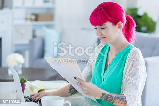 518704237istockphoto Artistic young woman works on computer at home 872120630