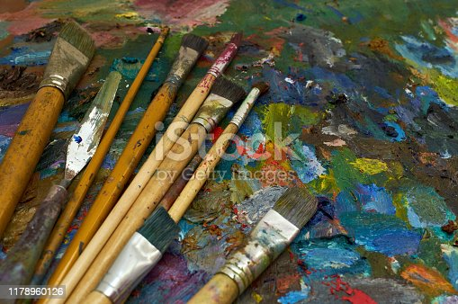 577949148istockphoto artists brushes and oil paints on palette 1178960126