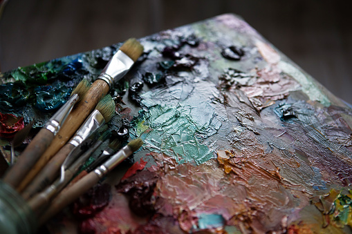 577949148 istock photo artists brushes and oil paints on wooden palette 577949180