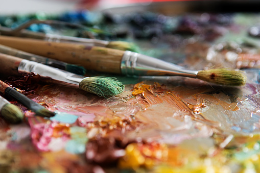 577949148 istock photo artists brushes and oil paints on wooden palette 577949212
