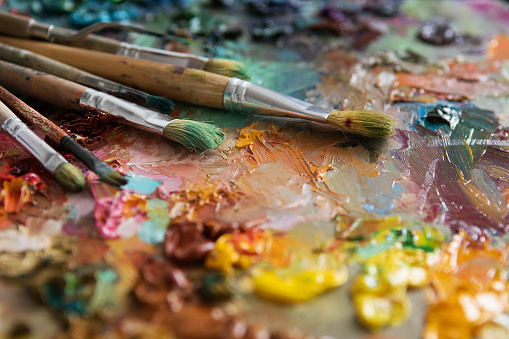 577949148 istock photo artists brushes and oil paints on wooden palette 577949282