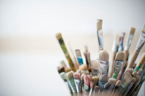 Close up of a series of used brushes in an artist's studio.