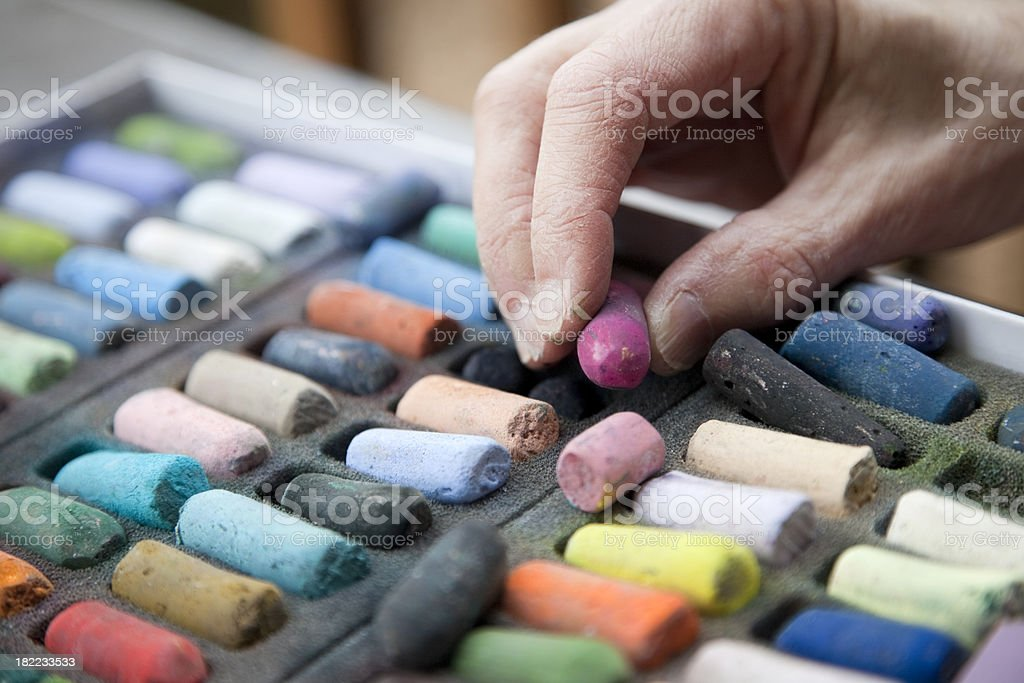Artist's Hand Reaching for a Pink Pastel Crayon stock photo