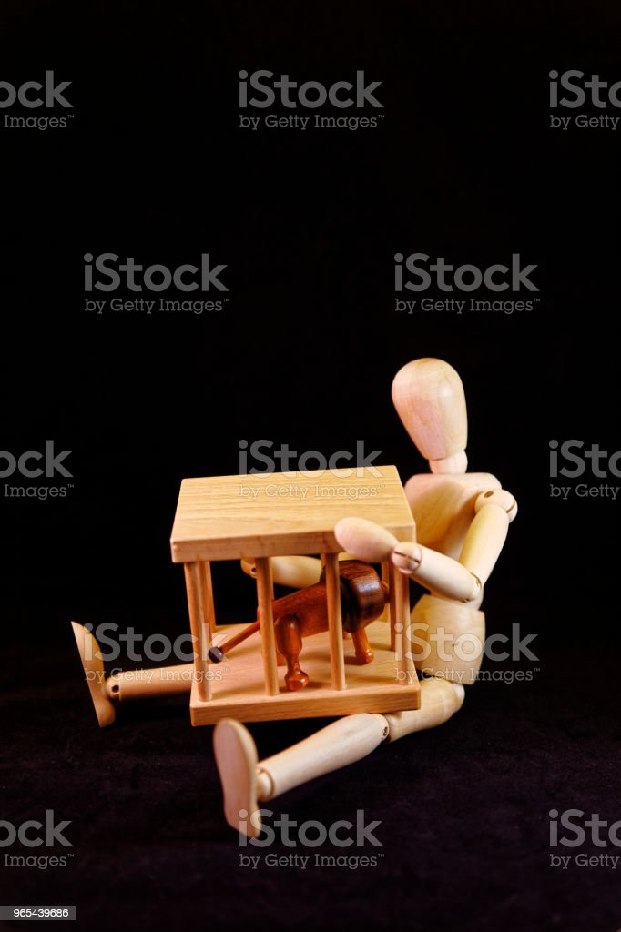 Artists mannequin sitting on the floor, holding a lion's cage royalty-free stock photo