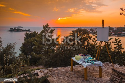 Artist's equipment set up outdoors with beautiful sunset in the distance