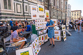 Florence, Italy - August 16, 2019: Artists paint and sell their paintings by the wall Cathedral Santa Maria Del Fiore in Florence, Tuscany, Italy