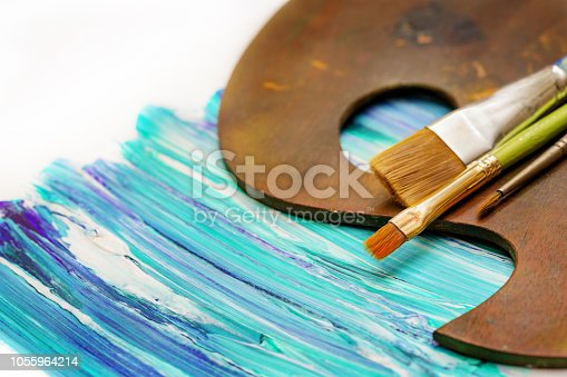 Artist's palette and paint brushes on an abstract blue and green painting