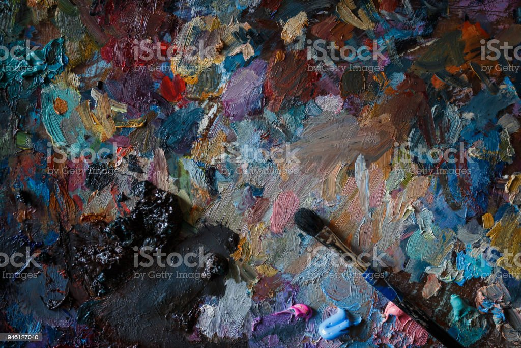 Artist's palette with multi-colored smeared colors and one brush. Close up. stock photo