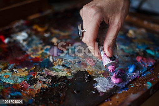 istock Artist's palette with multi-colored smeared colors and one brush. 1091701004