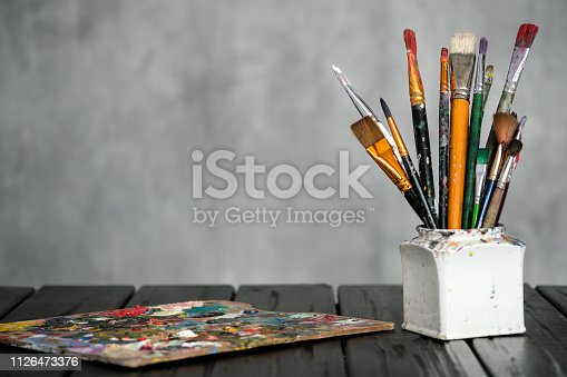 istock Artist's tools, brushes, paints and a palette lie on a black wooden table on a gray fabric background. 1126473376