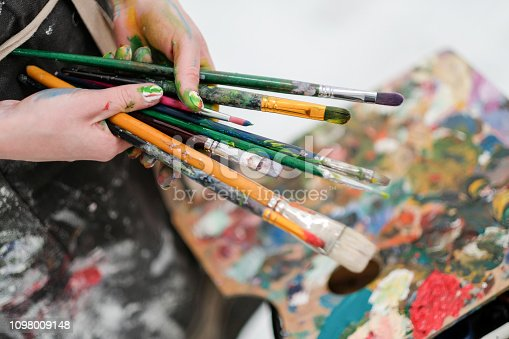 istock Artist's tools on the easel. Brushes, paints and canvas. 1098009148