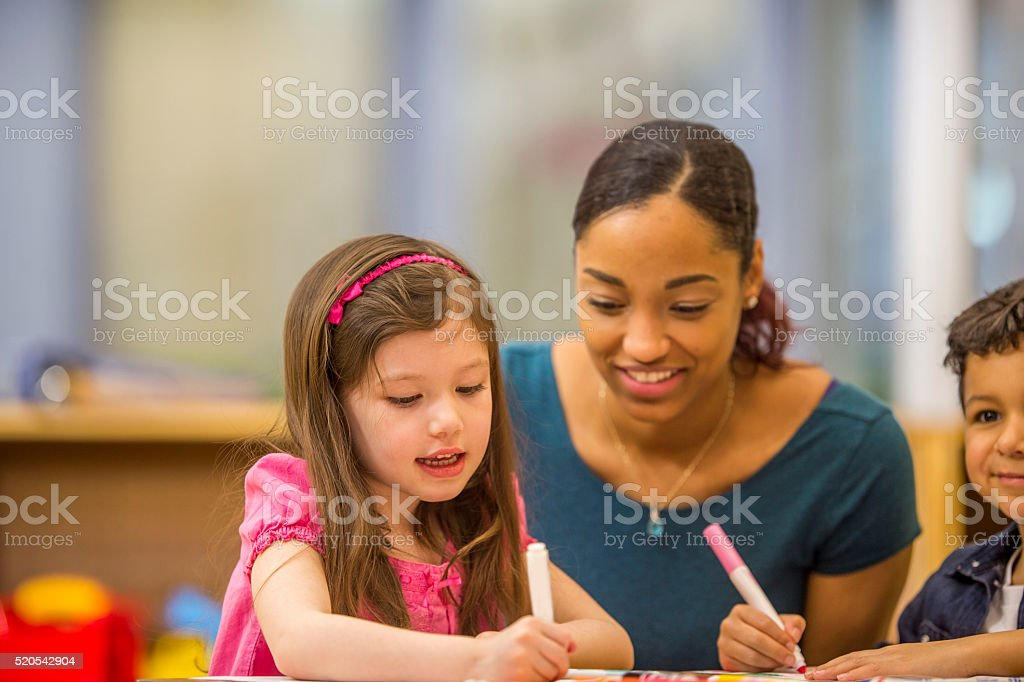 A multi-ethnic group of elementary age children are at their desk and...