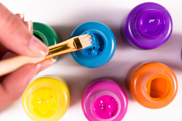 arts and crafts: paintbrush with multiple colored jars. creative hobby. - tempera painting stock pictures, royalty-free photos & images