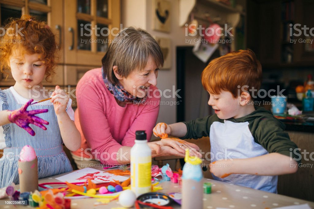 Grandma and her young grandchildren playing with arts and crafts at...
