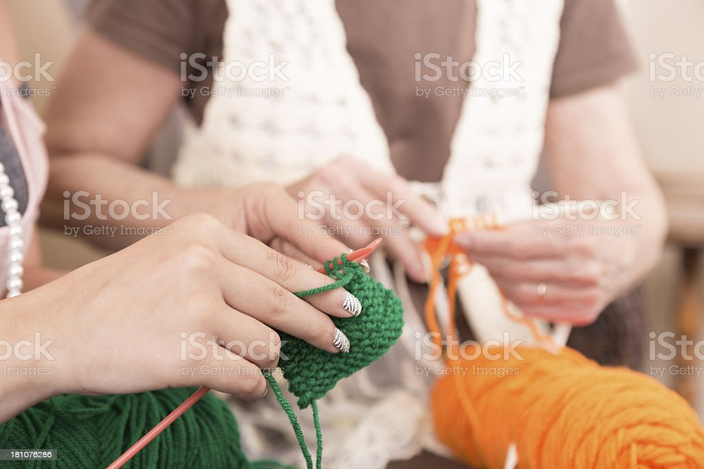 Arts Crafts: Young adult and senior knitting together. royalty-free stock photo