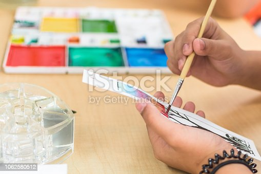 istock Arts painting class in school with young student's hand using brush coloring watercolor paint on craft drawing paper 1062580512