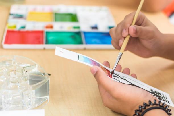 kunst malerei klasse in der schule mit jungen studenten hand mit pinsel färbung aquarellfarbe auf zeichenpapier handwerk - high school bilder stock-fotos und bilder