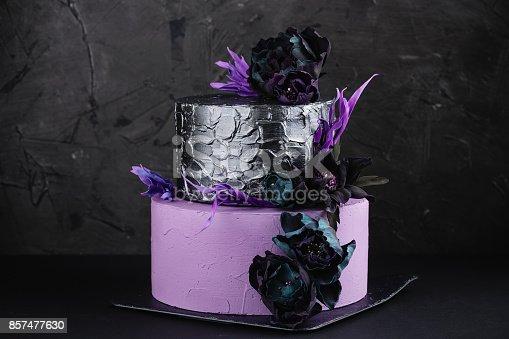 istock Artwork wedding cake with fake flowers on black background 857477630