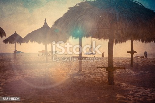 Vintage texture style view of tropical beach with grass hut palapas at sunset with lens flare