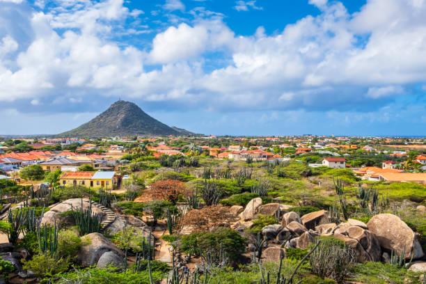 aruba, casibari rotsformatie met hooiberg vulkanische vorming in de achtergrond - aruba stockfoto's en -beelden