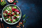 Arugula, Beet and cheese salad with fresh radicchio and walnuts on plate with fork, dressing and spices on blue kitchen table background, place for text, top view