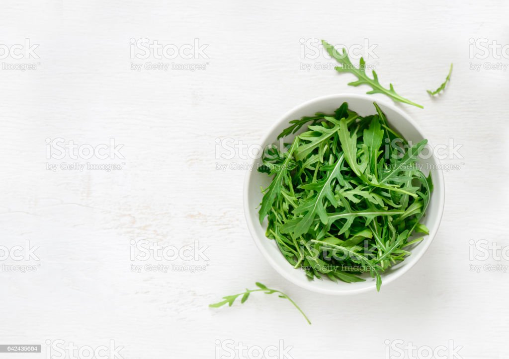 Arugula in a white bowl stock photo