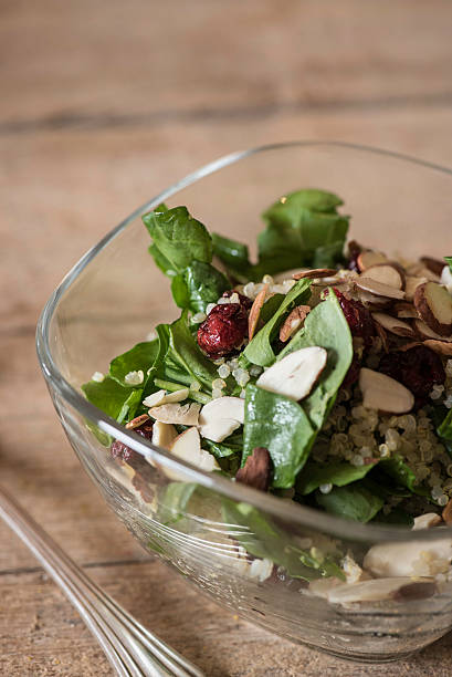 Arugula Quinoa Salad with Sliced Almonds and Cranberries Fresh arugula quinoa salad with sliced almonds and cranberries in a clear bowl with copy space above. quinoa stock pictures, royalty-free photos & images