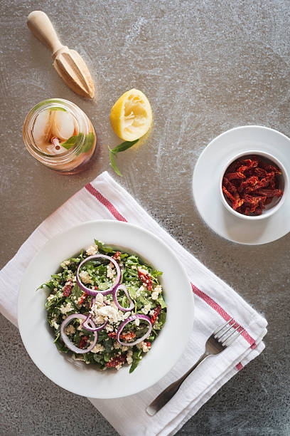 Arugula Quinoa Salad with Sun Dried Tomatoes A salad of arugula and quinoa with sun dried tomatoes, red onions and feta cheese topped with a lemon vinaigrette. quinoa stock pictures, royalty-free photos & images