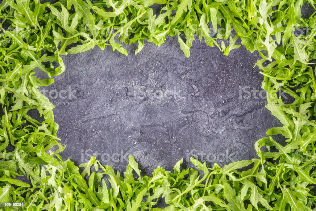 Arugula salad rucola leaves frame food background stock photo