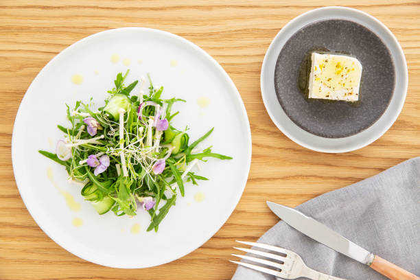 Arugula salad with bean sprout, enoki mushrooms, cucumber and edible flowers, feta cheese on the side over a wood background. Napkin, knife and fork. Flat lay. Vegetarian recipe. stock photo