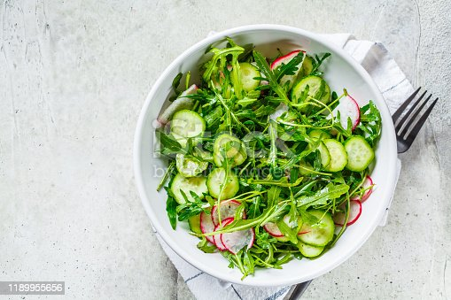 Arugula salad with cucumber and radish. Healthy vegan food concept.