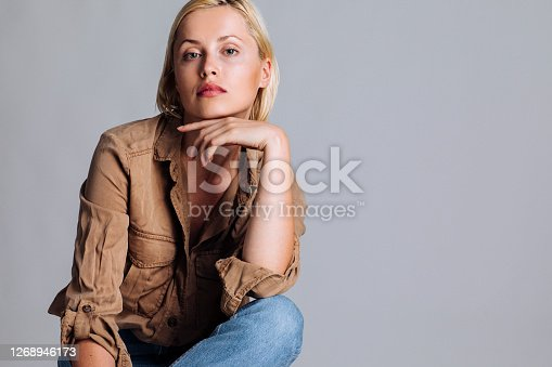 Female blond model sitting on a chair and posing for a studio photo